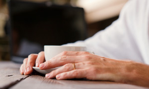 Close up image man hands with cup of coffee late breakfast