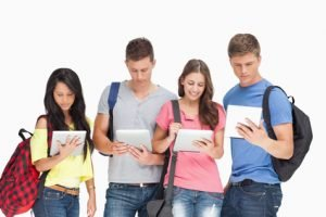 A group of students looking at their tablet pc's with backpacks on ergonomics in the classroom