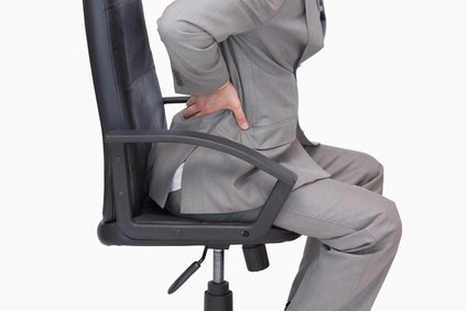 Businessman sitting long hours experiencing back pain.