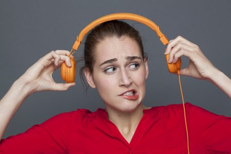 woman looking oddly at headphones