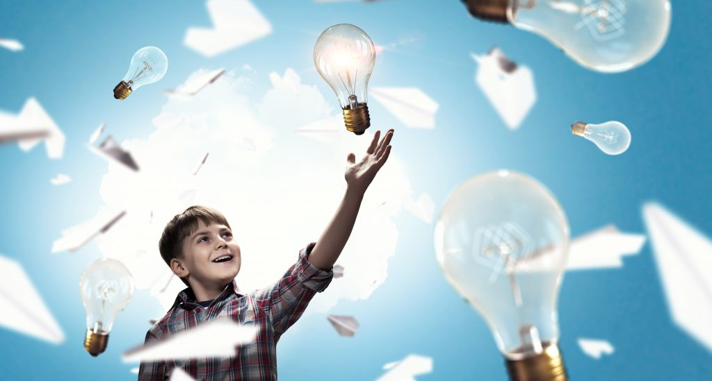 child in middle of light bulbs and paper airplanes - image to represent dreams
