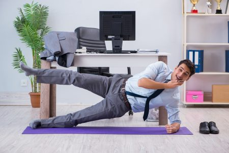 employee exercising at office while on smartphone