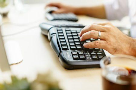 man typing on ergonomic keyboard