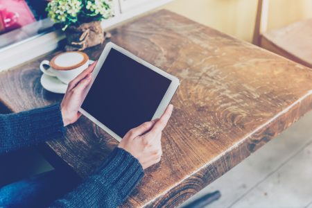 man holding tablet at coffee shop