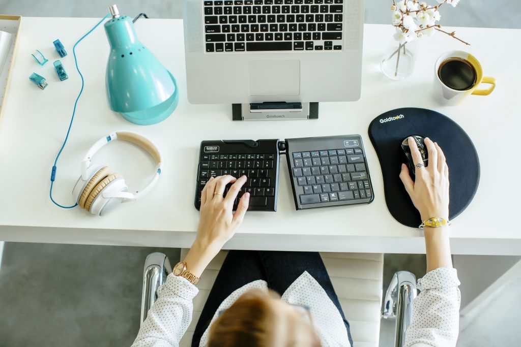 overhead view of woman at workspace using ergonomic keyboard and mouse