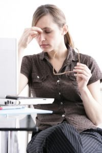 woman pinching nose after taking glasses off at desk