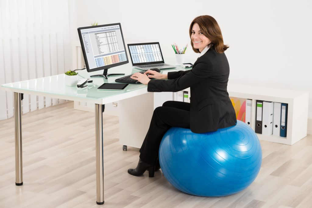 Young Businesswoman Sitting On Pilates Ball Working In Office