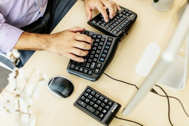 man at desk using ergonomic keyboard, mouse and numeric pad