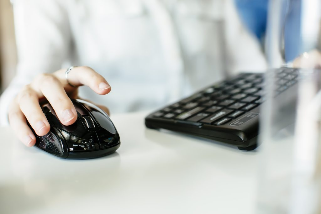 person using wireless mouse at computer workstation