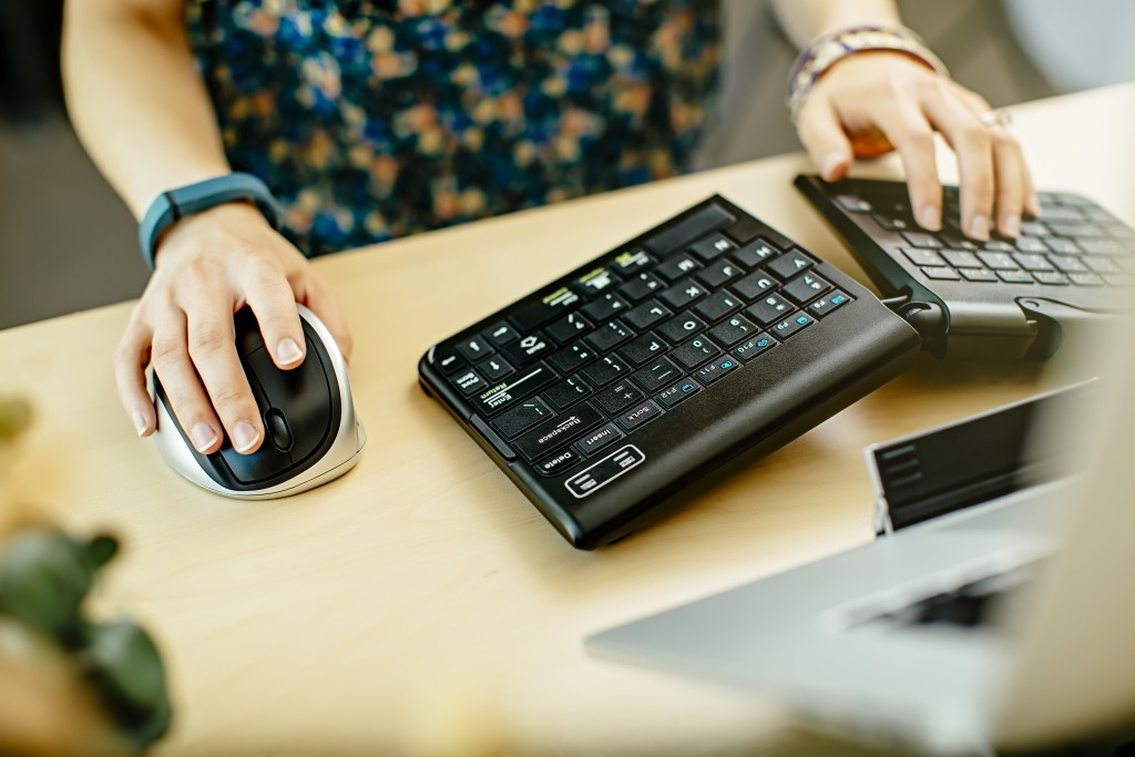 woman at desk with keyboard and mouse