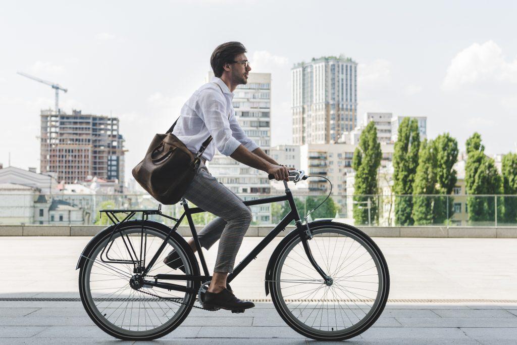 man biking to work with satchel over shoulder