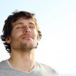 man with eyes closed taking in air