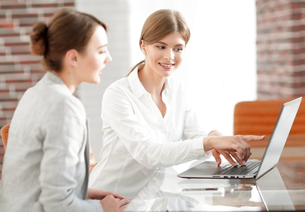 employees working on laptop at desk