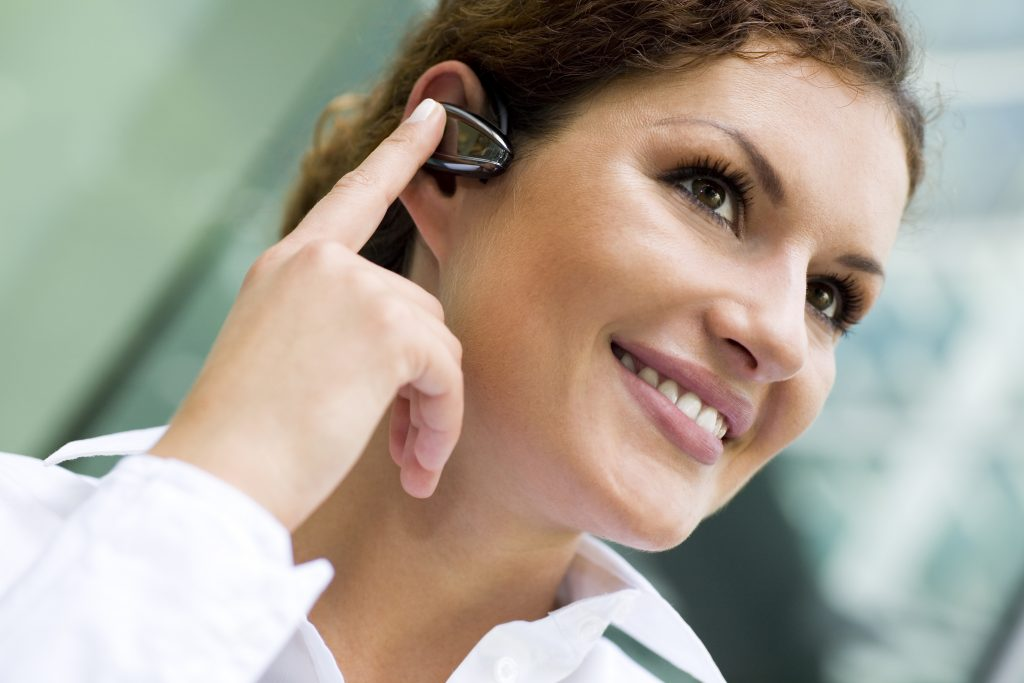 woman with Bluetooth headphone in ear