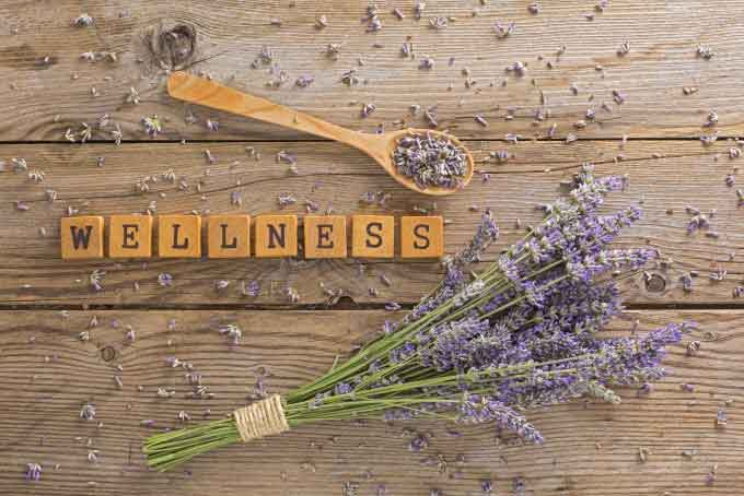 wellness spelled in scrabble tiles next to spoon and flowers