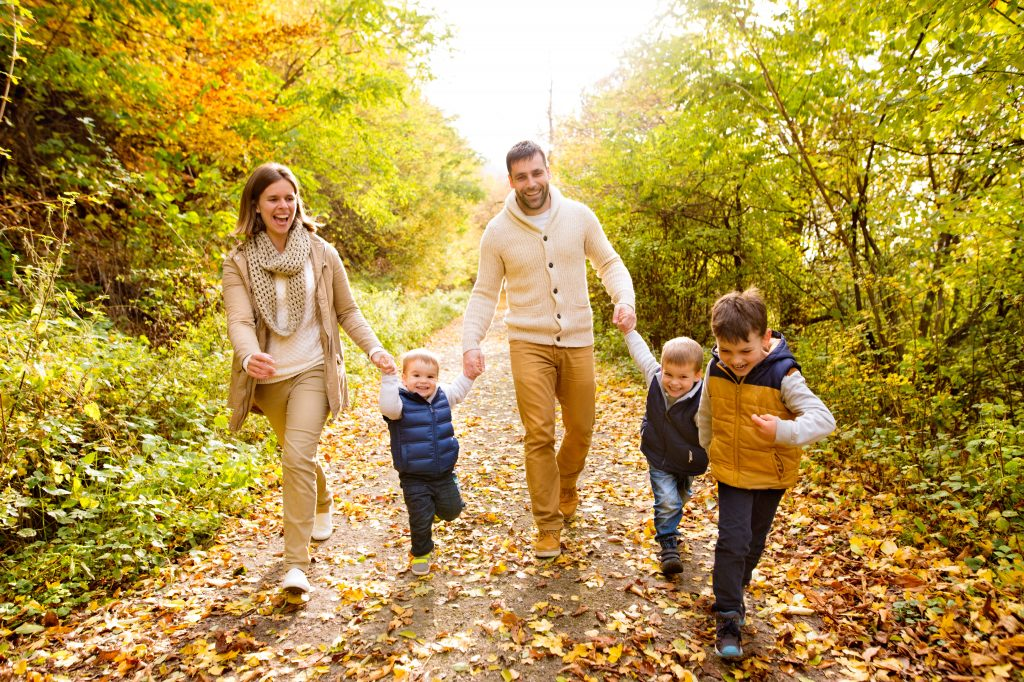 Beautiful young family on a walk in forest. Mother and father with their three sons in warm clothes outside in colorful autumn nature.