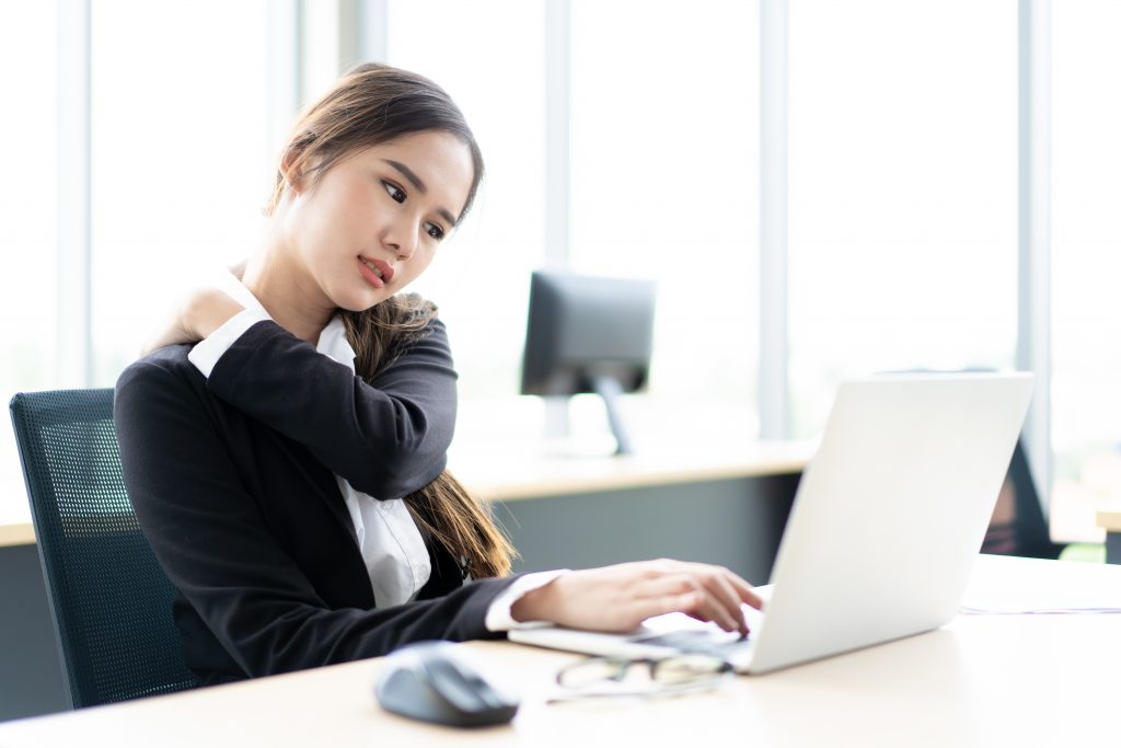 Woman working at desk on a laptop with shoulder pain.