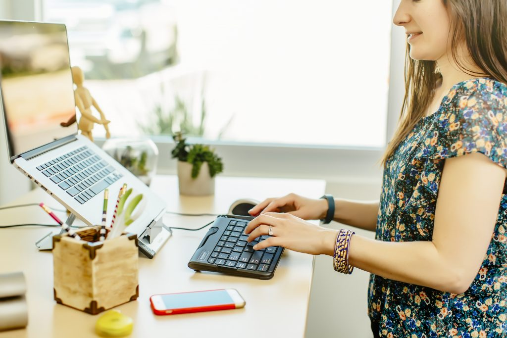 Woman working at a desk using ergonomic devices.